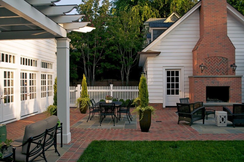 Inspiration for a timeless brick patio remodel in Charlotte with a fire pit