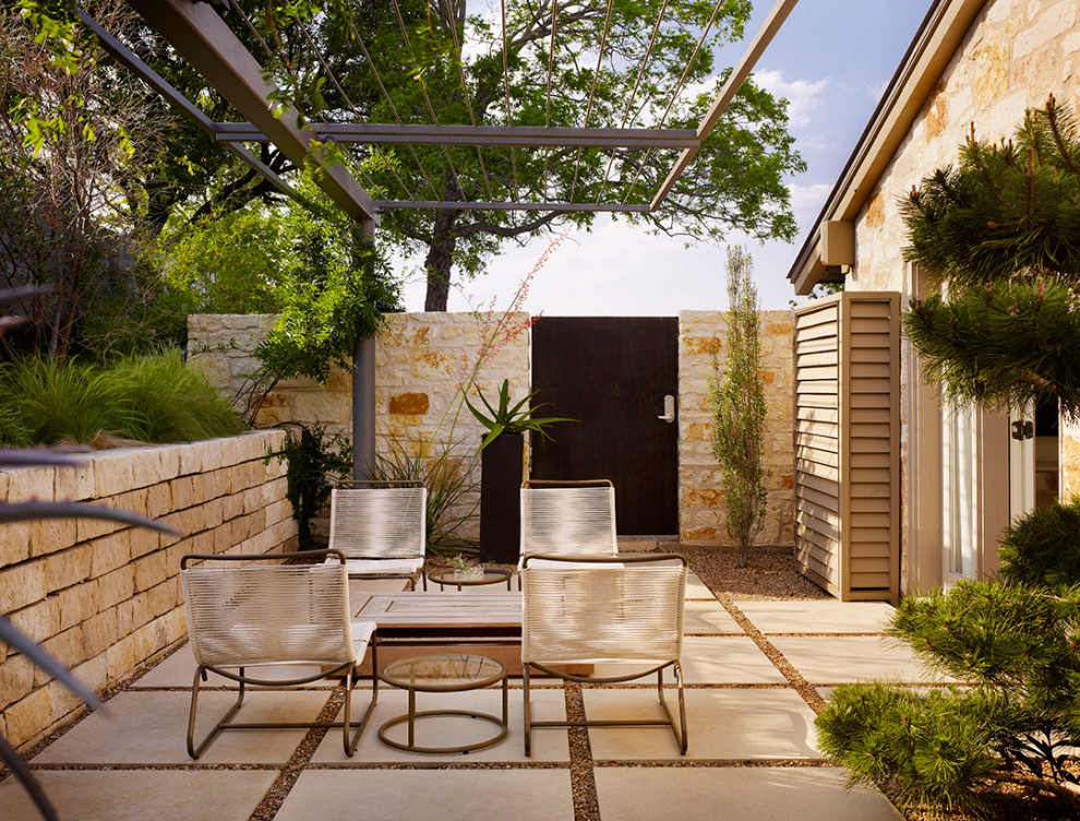 Patio - 1960s side yard patio idea in Austin with a pergola