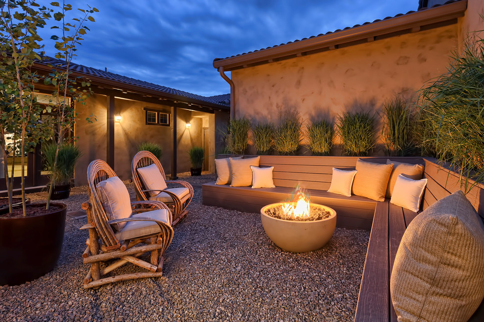 Patio - large southwestern courtyard gravel patio idea in Denver with a fire pit