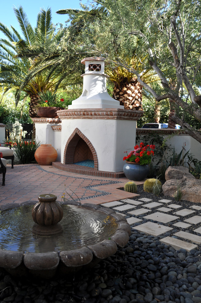 Example of a mid-sized tuscan courtyard tile patio design in Phoenix with a fire pit and no cover