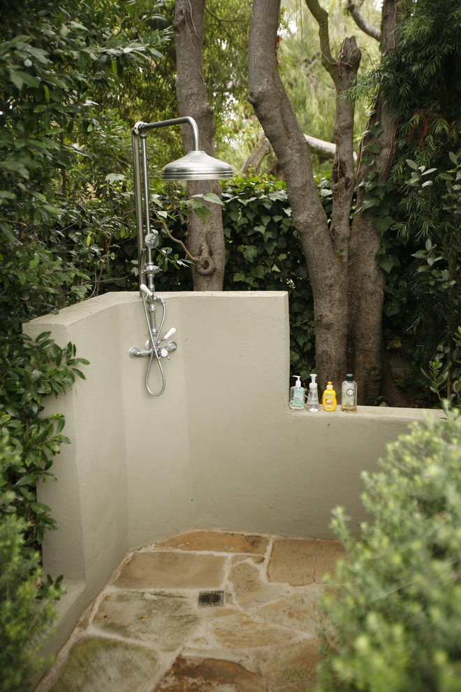 Example of a classic backyard stone outdoor patio shower design in Los Angeles