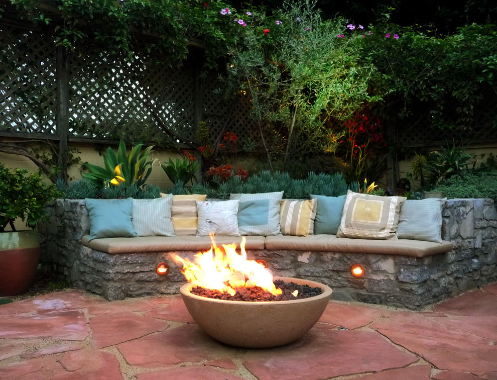 Large tuscan backyard stone patio photo in Los Angeles with a fire pit and no cover