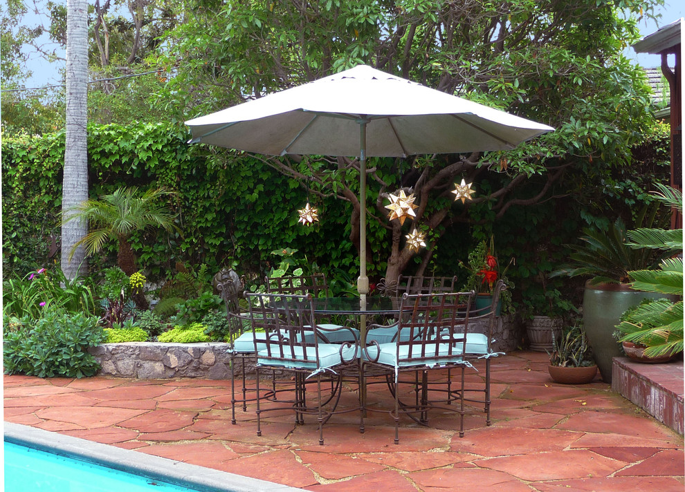 Inspiration for a large mediterranean backyard stone patio kitchen remodel in Los Angeles with no cover
