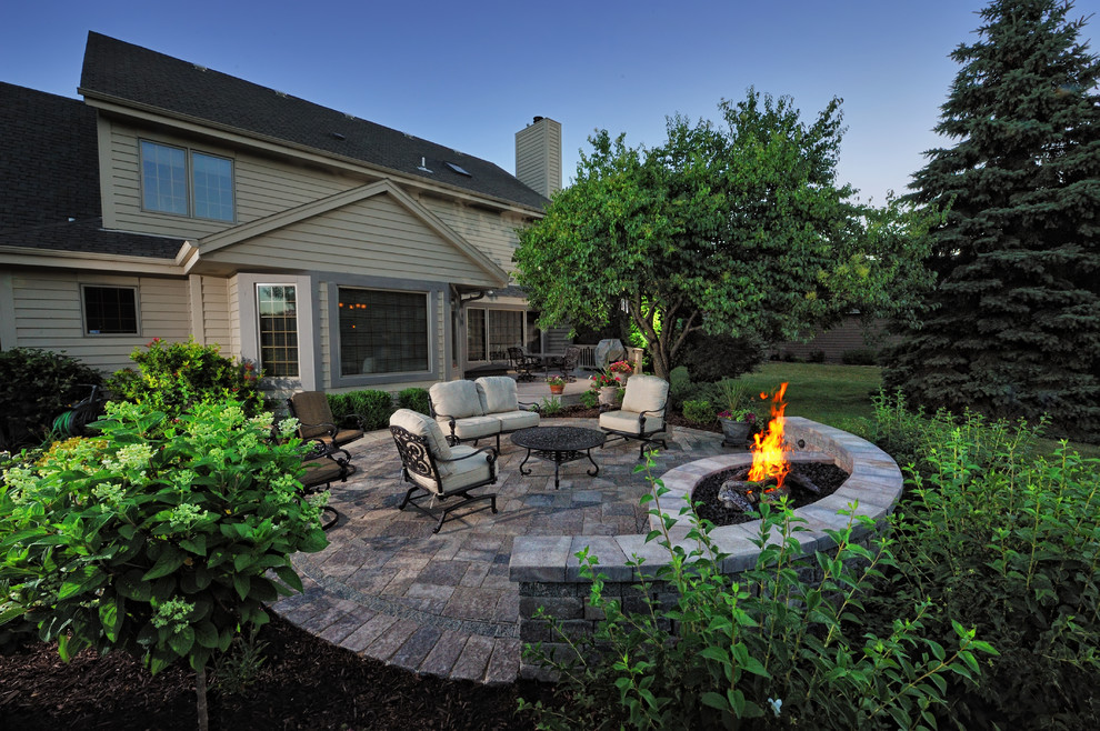 Inspiration for a mid-sized timeless backyard concrete paver patio remodel in Milwaukee with no cover and a fire pit