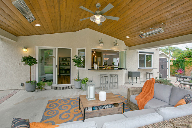 Example of a large classic backyard concrete patio design in San Diego with a roof extension