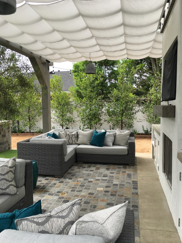 Example of a mid-sized beach style backyard stone patio design in Orange County with an awning