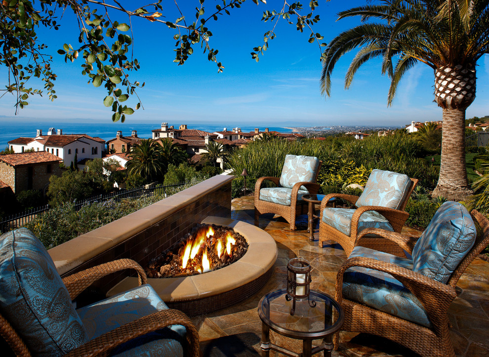 Example of a tuscan backyard patio design in Orange County with a fire pit