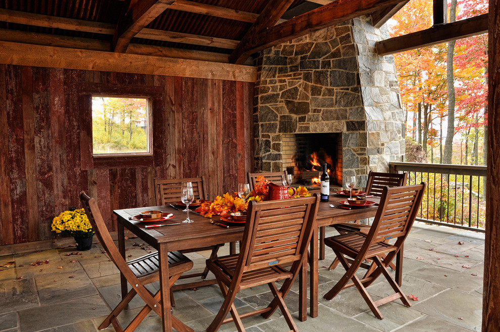 Inspiration for a rustic patio remodel in Baltimore with a roof extension and a fireplace