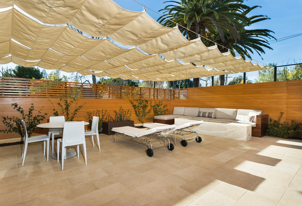 Photo of a mid-sized modern patio in Los Angeles with tile and an awning.