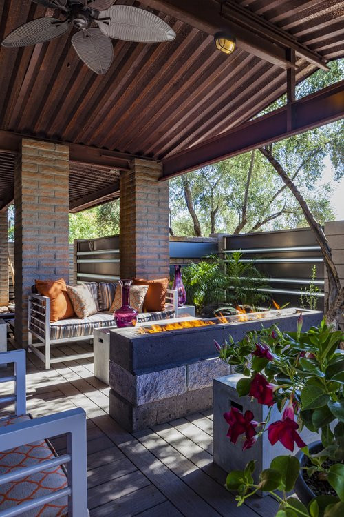 Mid-sized urban courtyard patio photo in Phoenix with a fire pit, decking and a roof extension