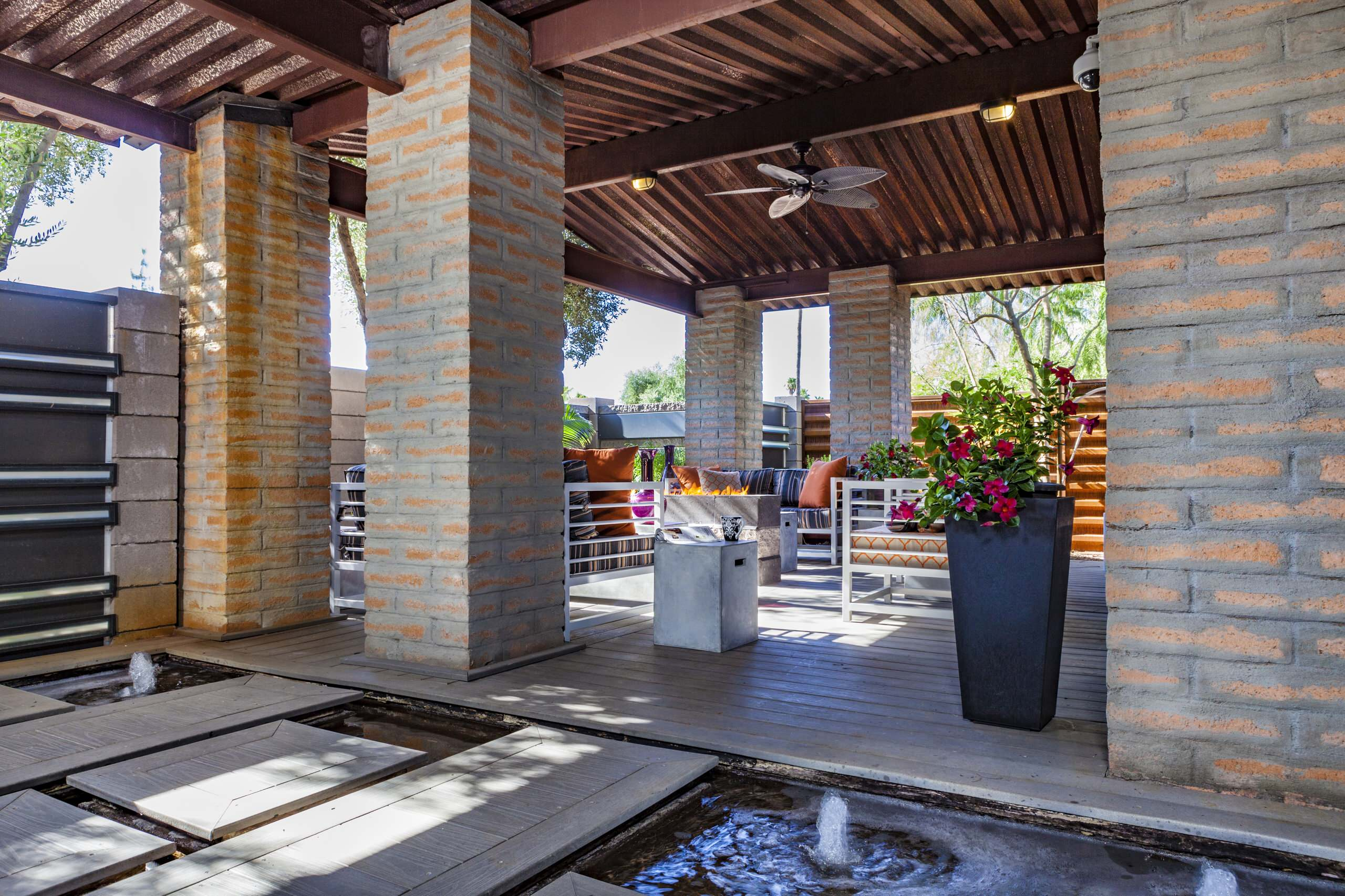 Inspiration for a mid-sized industrial courtyard patio remodel in Phoenix with decking and a roof extension
