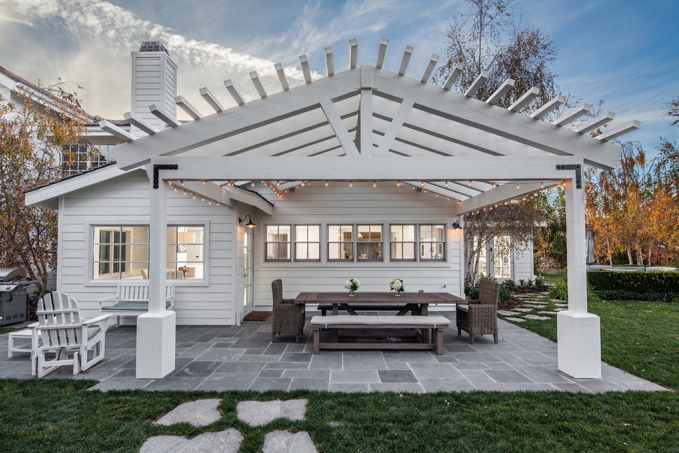 Mid-sized country backyard stone patio photo in San Diego with a pergola