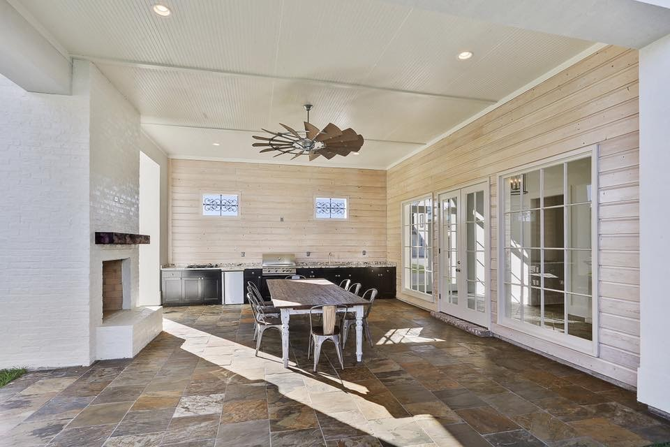 Example of a large classic backyard stone patio kitchen design in New Orleans with a roof extension