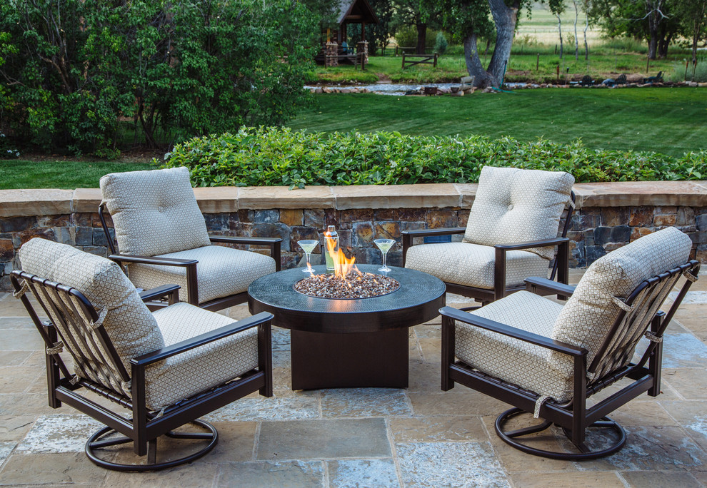 Patio - small rustic backyard stone patio idea in Denver with a fire pit and no cover