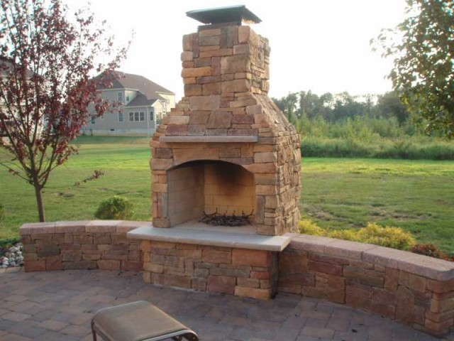 Outdoor fireplace with custom brick design elements in new for Outdoor stone fireplace designs