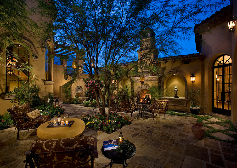 Example of a huge classic courtyard stone patio design in Phoenix with a fire pit