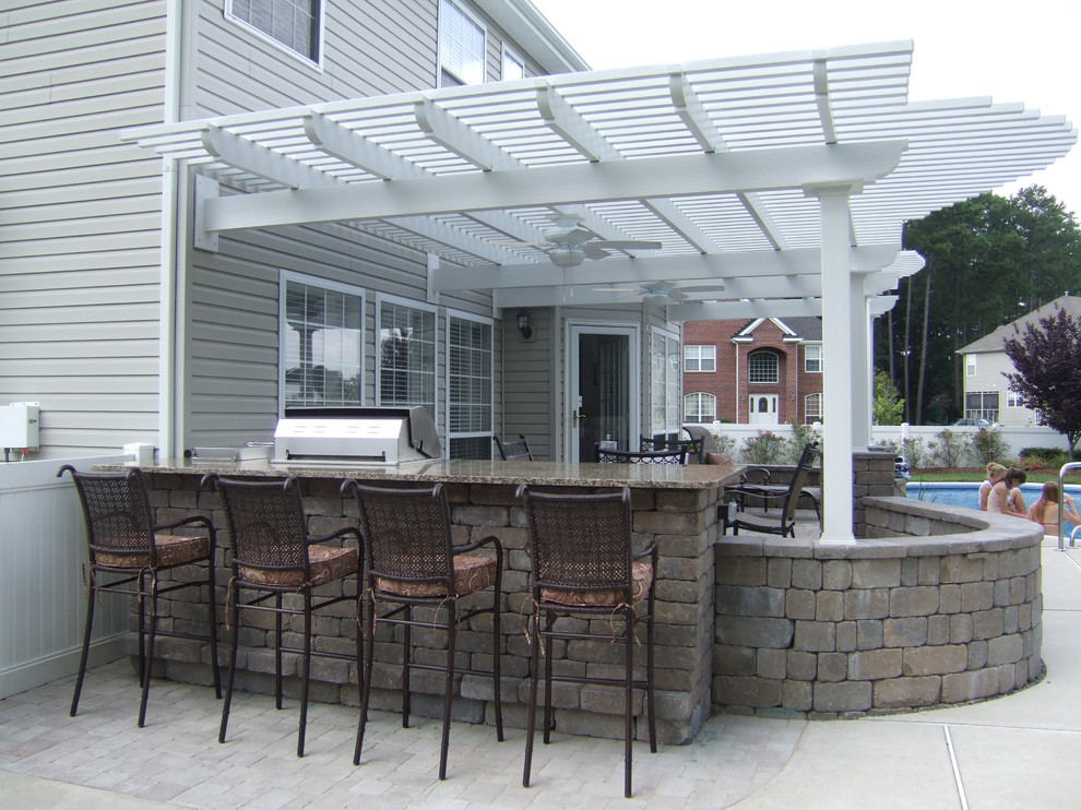 Patio kitchen - large traditional backyard concrete patio kitchen idea in Other with a pergola