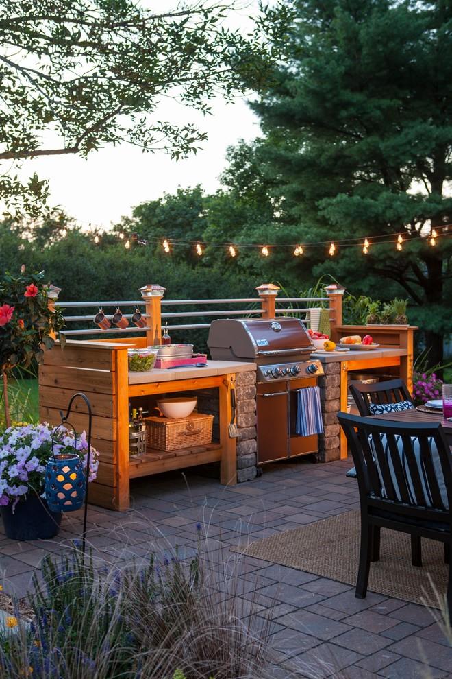Small urban backyard brick patio kitchen photo in Other
