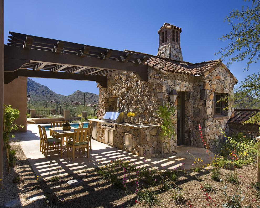 Patio kitchen - traditional patio kitchen idea in Phoenix with a pergola