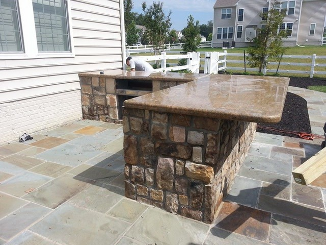 Outdoor Kitchen With Bar And Granite Countertops