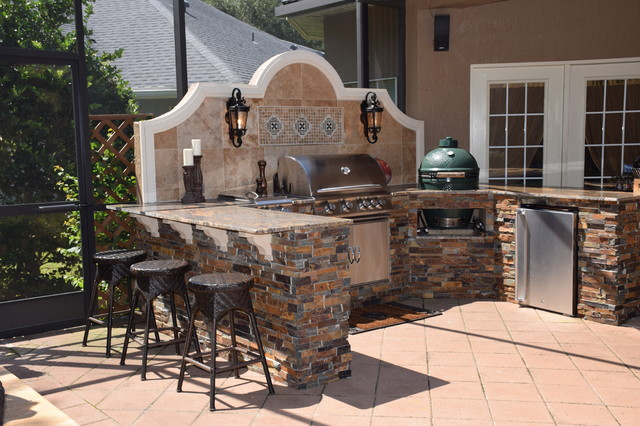 Outdoor kitchen with Big Green Egg, gas grill and bar seating.