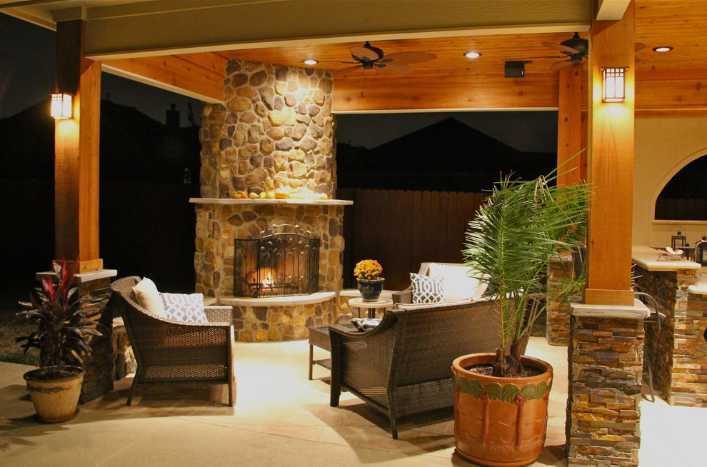 Patio - large contemporary backyard stone patio idea in Houston with a fire pit and a roof extension