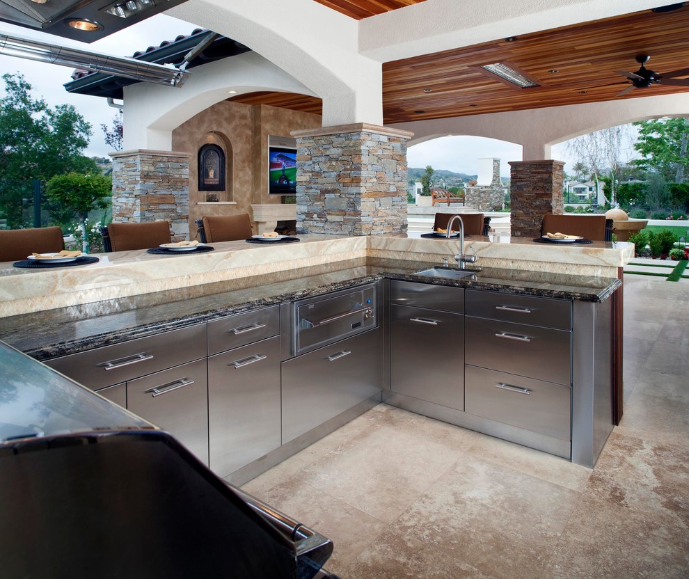 Example of a huge mountain style backyard stone patio kitchen design in Orange County with a roof extension