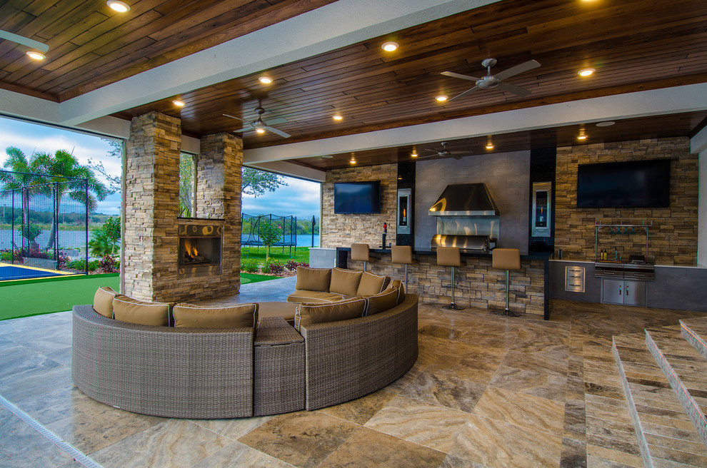 Huge trendy backyard stone patio kitchen photo in Tampa with a roof extension