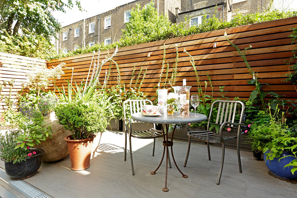 Example of a transitional patio design in London with no cover