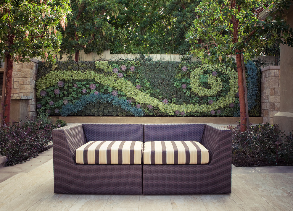 plants growing on wall in artistic pattern in patio behind furniture