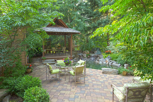 garden courtyard patio design surrounded by plants and covered seating