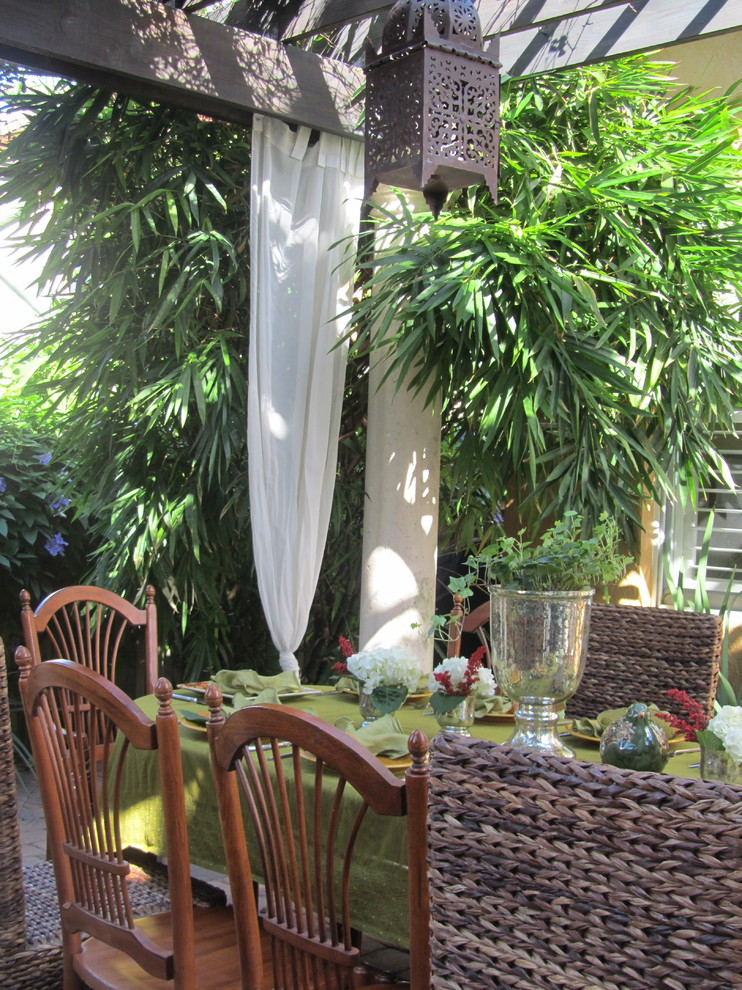 Example of an island style patio design in Miami with a pergola