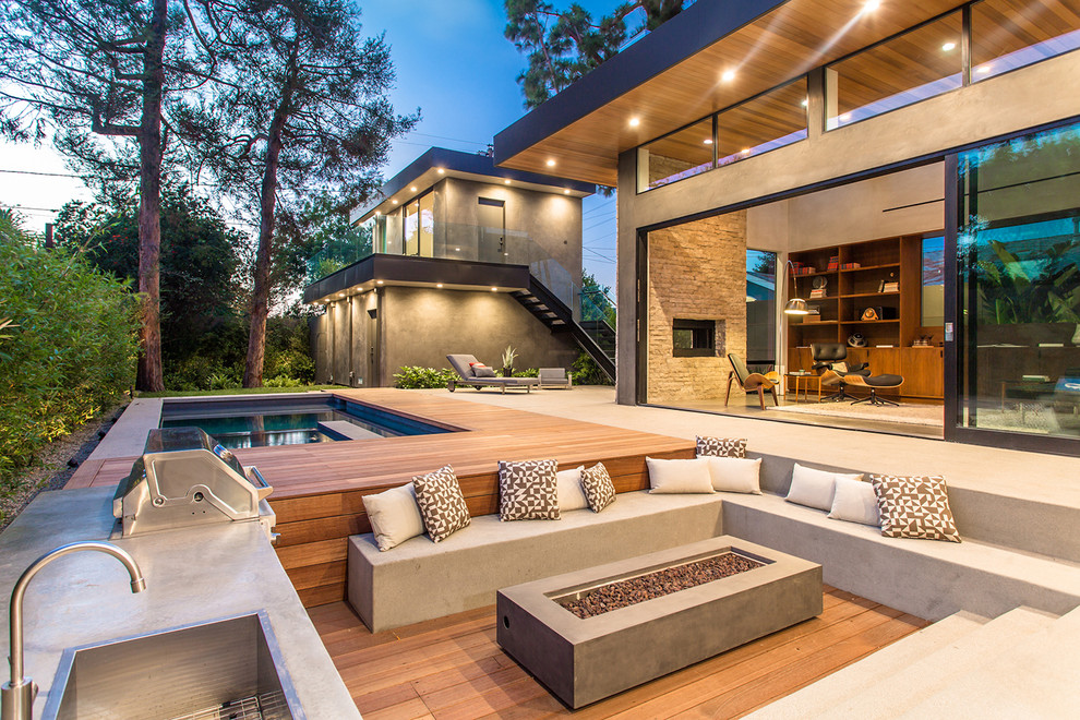 Inspiration for a contemporary backyard patio kitchen remodel in Los Angeles with decking and no cover