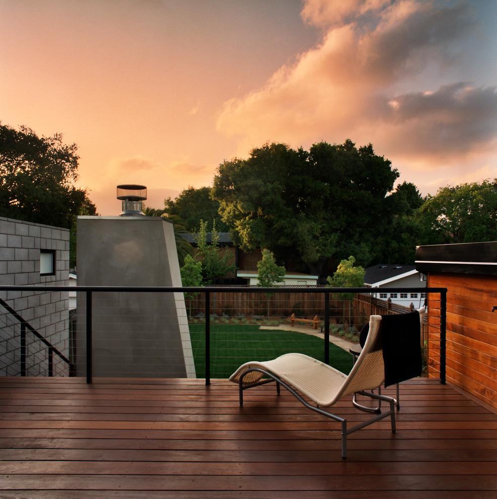 Cette image montre une terrasse arrière design avec un foyer extérieur.