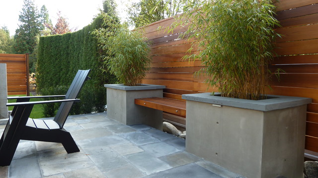 Example of a mid-sized arts and crafts backyard stone patio design in Vancouver with a fire pit and a roof extension