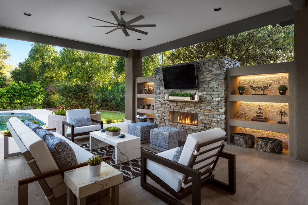Patio - large contemporary backyard tile patio idea in Phoenix with a roof extension and a fireplace