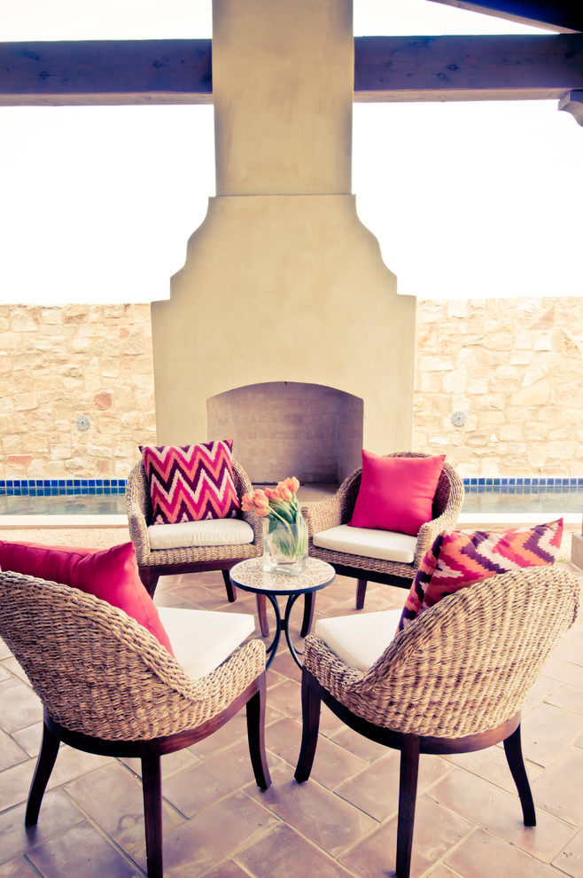 Example of a tuscan patio design in Austin with a fire pit