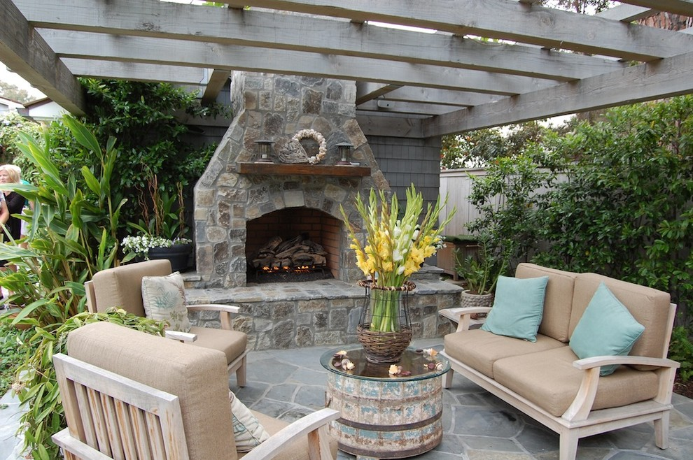 Beach style patio photo in Orange County with a fire pit and a pergola