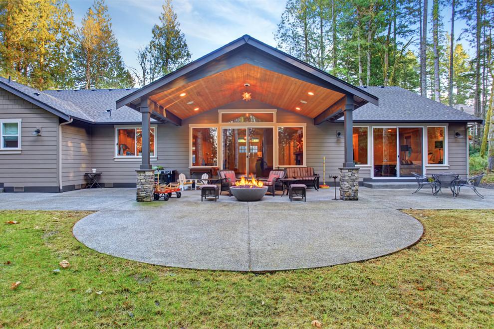 Ispirazione per un grande patio o portico stile americano dietro casa con un focolare, lastre di cemento e un tetto a sbalzo