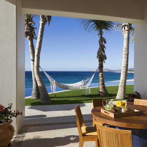 hamaca colgada de dos palmeras en una casa de playa