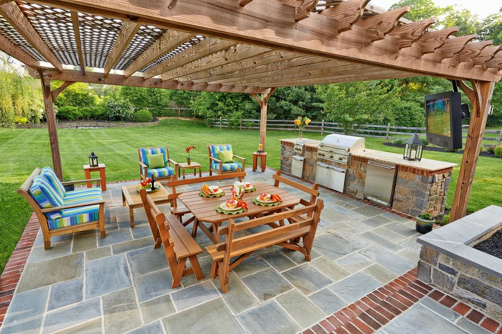 Patio kitchen - traditional stone patio kitchen idea in Wilmington with a pergola