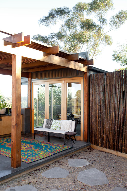 A tall mahogany stained bamboo privacy wall that shades this lovely patio from any neighbor's eyes. The rich dark stain matches the rest of the wooden roof and supports of the patio.