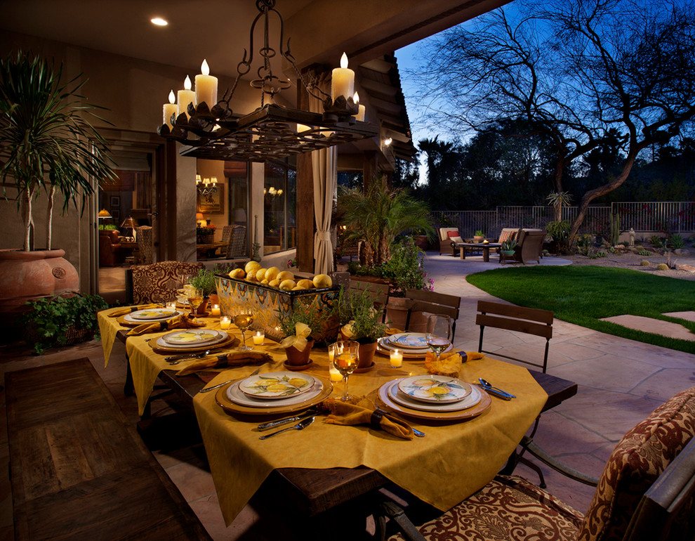 Patio - mediterranean backyard stone patio idea in Phoenix with a roof extension