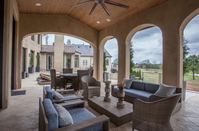 Large tuscan backyard stone patio photo in Other with a fireplace and a roof extension