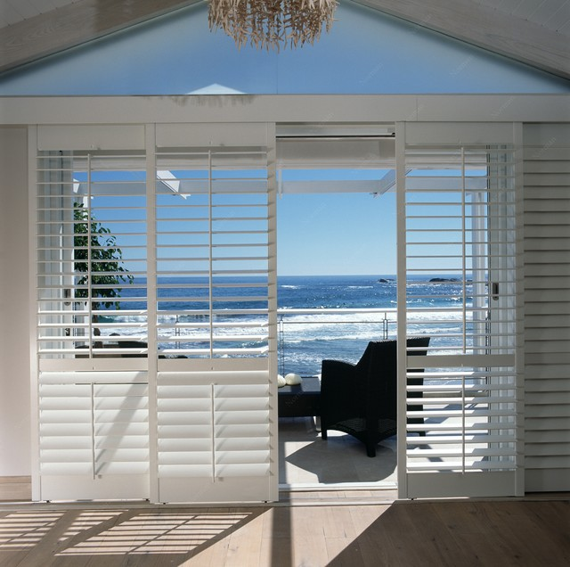 Plantation shutters beach style patio brisbane by for Beachy exterior shutters