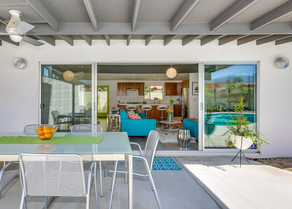 Patio - mid-sized mid-century modern backyard concrete paver patio idea in Los Angeles with a roof extension