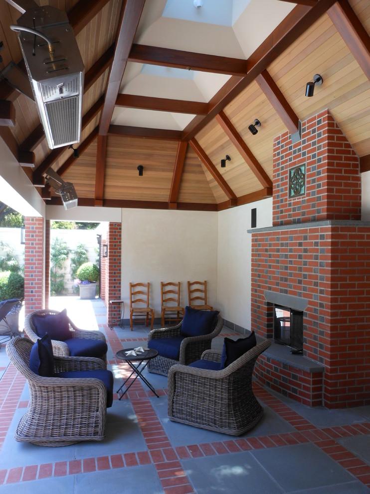 Esempio di un patio o portico tradizionale di medie dimensioni e dietro casa con un focolare, pavimentazioni in cemento e un tetto a sbalzo