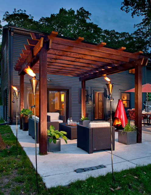 Inspiration for a mid-sized contemporary backyard concrete patio remodel in Milwaukee with a fire pit and a pergola