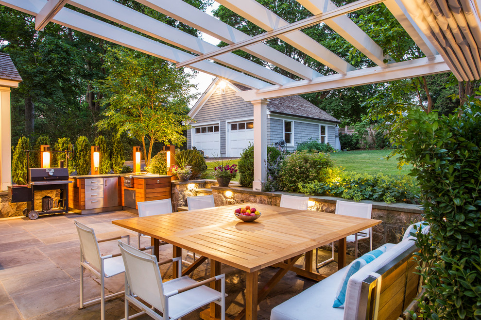 Example of a mid-sized classic backyard stone patio design in New York with a pergola