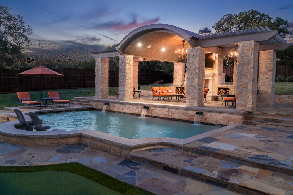 Large backyard stone patio photo in Dallas with a fireplace and a gazebo